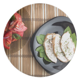Сhicken meat decorated with basil and tomato salad plates