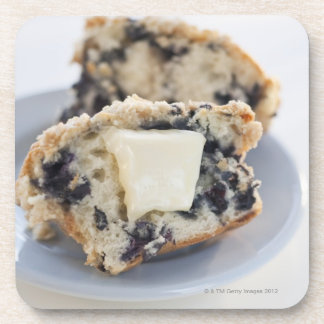 A blueberry muffin with butter coaster