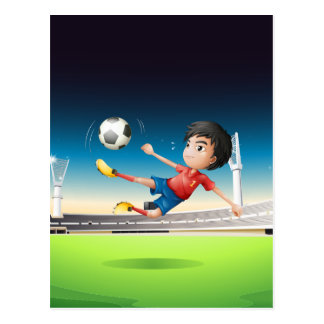A boy in a red uniform at the soccer field postcard