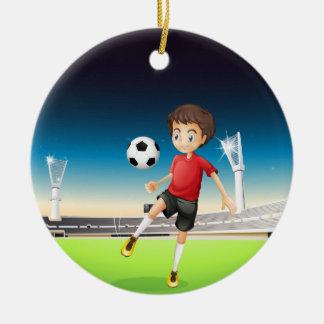A boy playing soccer alone ceramic ornament