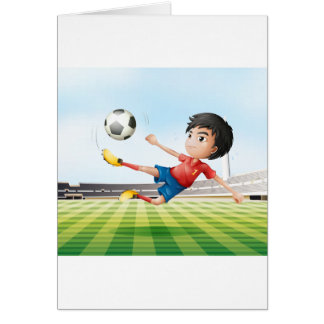 A boy playing soccer in the soccer field card