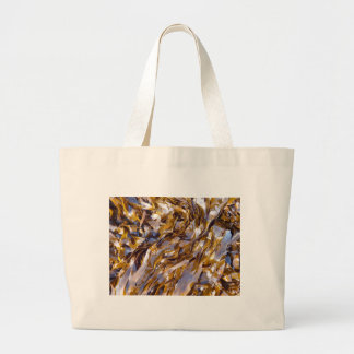 A brown seaweed on the surface of the sea. large tote bag