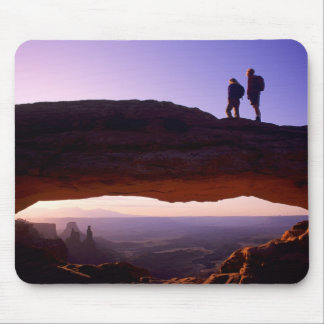 A couple watches sunrise from atop Mesa Arch in Mouse Pad