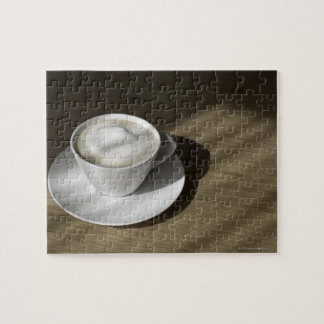 A cup of cappuccino coffee lies on an oak jigsaw puzzle