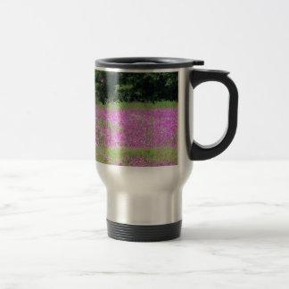 A field of pink spring wildflowers travel mug