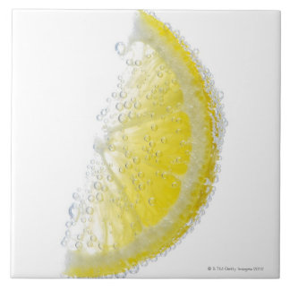 A juicy ripe organic lemon wedge fruit submerged tile