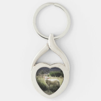a little white lamb behind a fence in a field Silver-Colored twisted heart keychain