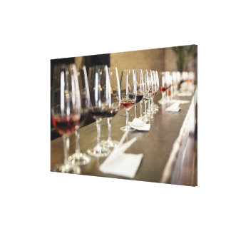 A long row of wine glasses set up so a large canvas print