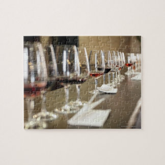 A long row of wine glasses set up so a large jigsaw puzzle