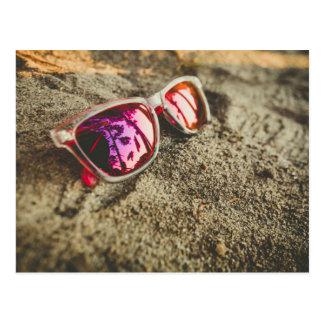 A Pair Of Fashionable Sunglasses On The Beach Postcard