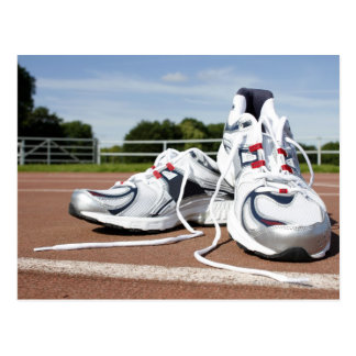 A pair of new white running trainers are placed postcard