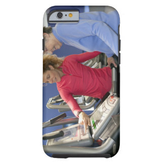 A personal trainer helps a senior woman on a tough iPhone 6 case