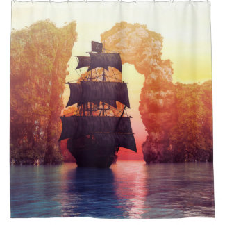A pirate ship off an island at a sunset