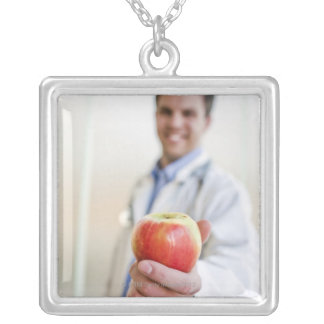 A portrait of a doctor holding a apple. square pendant necklace