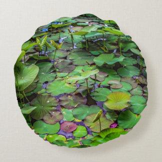 A pretty pond full of lily pads at a water temple round pillow