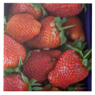 a punnet of ripe fresh strawberries for sale in tiles