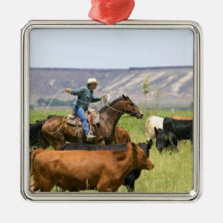 A rancher on horseback during a cattle roundup metal ornament