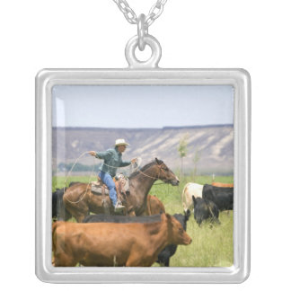 A rancher on horseback during a cattle roundup silver plated necklace