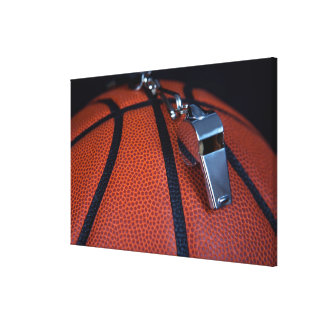 A referee's whistle rests on top of a gallery wrapped canvas