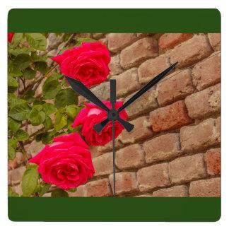 a roses climb on a brick wall  square wall clock