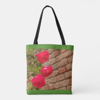 a roses climb on a brick wall tote bag