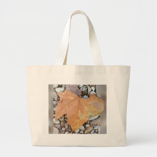 a rusty leaf on pebbles large tote bag