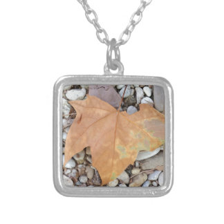 a rusty leaf on pebbles silver plated necklace