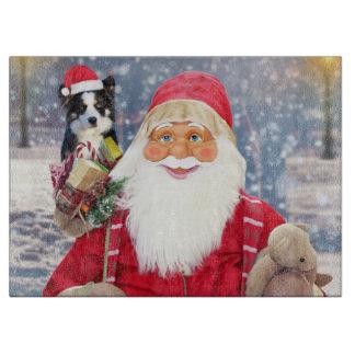 A santa claus holding a cute Border Collie and chr Cutting Board