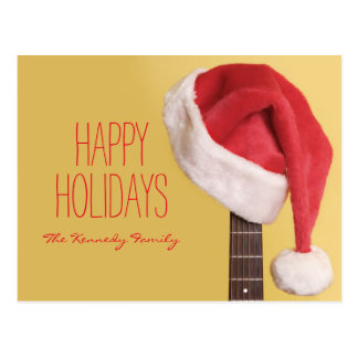 A Santa hat hangs on an acoustic guitar in front Postcard