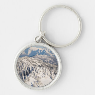 A Scenic View of Snowy Mountains and Trees. Silver-Colored Round Keychain