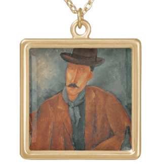 A seated man leaning on a table gold plated necklace