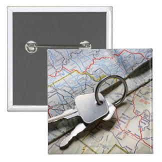 A set of car keys on a pile of road maps. 2 inch square button
