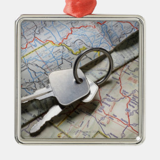 A set of car keys on a pile of road maps. metal ornament