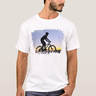 A silhouette of a mountain biker at sunset on T-Shirt