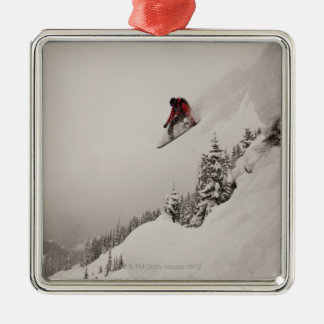 A snowboarder jumps off a cliff into powder in christmas tree ornament