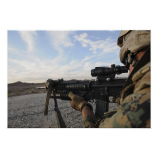 A soldier sights in to fire on a target poster