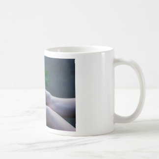A sprout on a hand coffee mug