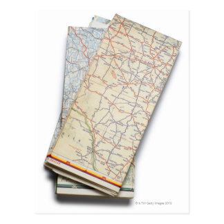 A stack of folded road maps on a white postcard