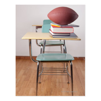 A student desk with a football sitting on a pile postcard