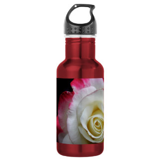 A water bottle close up of a red and white rose