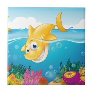A yellow shark diving into the sea tile