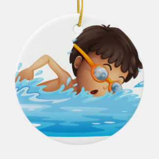 A young boy swimming with a yellow goggles round ceramic ornament