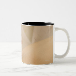 Acupuncturist putting needles in woman's back Two-Tone mug