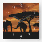 African elephants silhouettes in sunset square wall clock