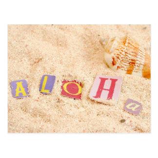Aloha on a sandy beach with seashells postcard
