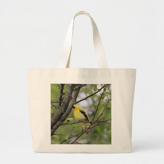 American goldfinch perched in a tree large tote bag