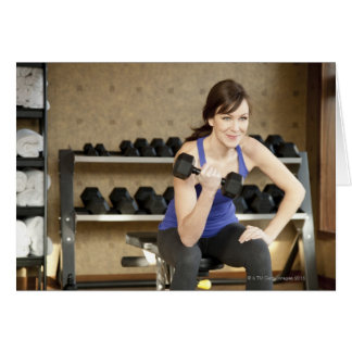 An active female lifting weights in a private card