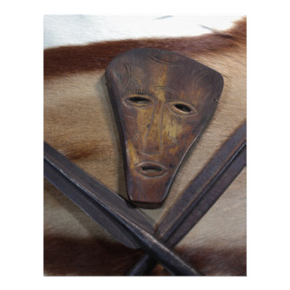 An African mask with a spear on an antelope skin. Letterhead