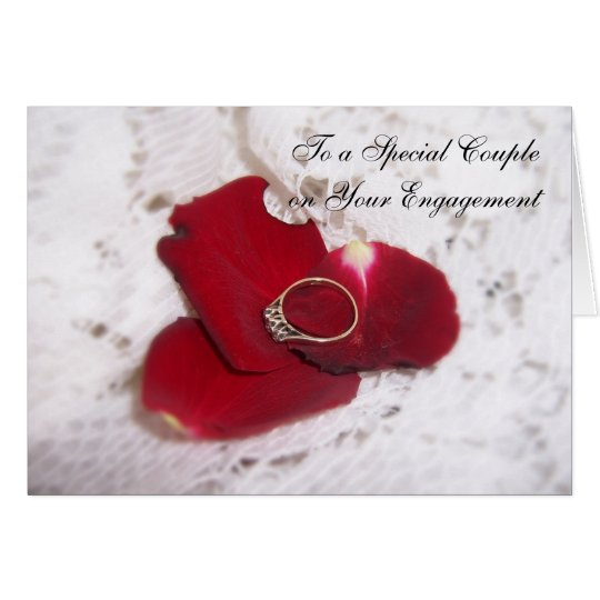An Engagement Card Diamond Ring And Rose Petals