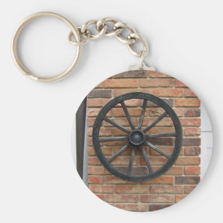 An old cart wheel on a brick wall keychain